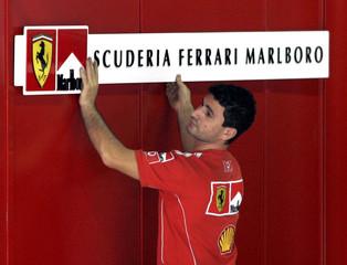 A Ferrari Formula One team member adjusts a team board in the team garage at the Interlagos race ...