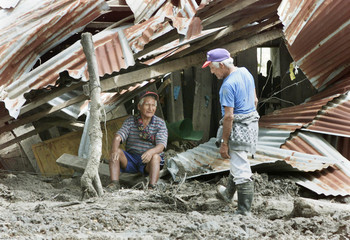 BOLIVIANS SIT AMONGST RUBBLE AFTER MUDSLIDE.