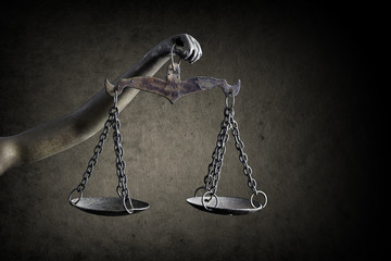 Lady Justice's hand holding Scale of Justice isolated on grunge background
