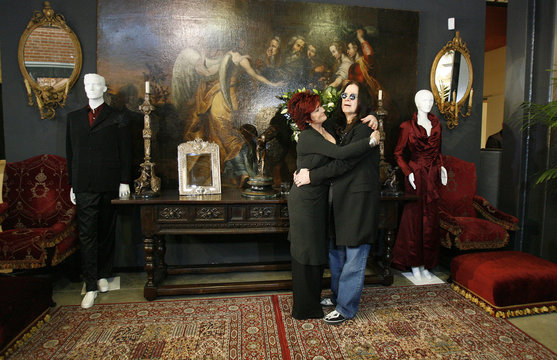 Ozzy and Sharon Osbourne pose in front of some of their belongings to be auctioned in Beverly Hills