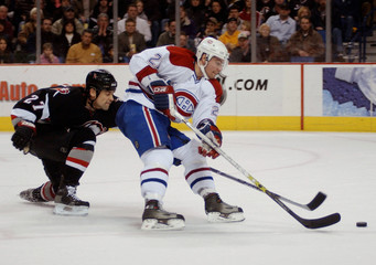 Sabres defenseman Numminen chases Canadiens center Higgins during  NHL game in Buffalo