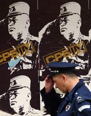 Serbian policeman adjusts his hat as walks past posters of war crimes fugitive Mladic in Belgrade