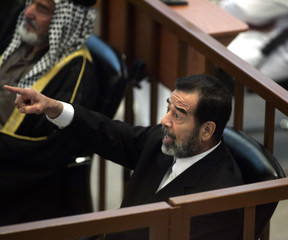 Former Iraqi President Saddam Hussein gestures as he attends his trial held in Baghdad's heavily fortified Green Zone