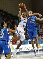 Batum of France goes for the basket past Zisis and Fotsis of Greece during their FIBA EuroBasket 2009 Qualifying Round Group E basketball game in Bydgoszcz