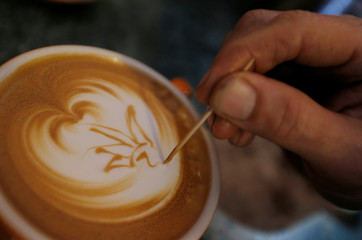 Barista Mark Zheng uses a toothpick to draw an image of the Sydney Opera House in the crema of a flat white coffee at Le Petit tarte coffee shop in Sydney