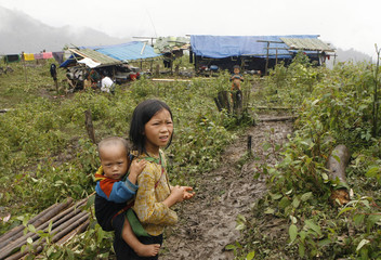 An ethnic Dao girl carries her brother in front of a makeshift camp for mountain landslide victims in Khen Len village