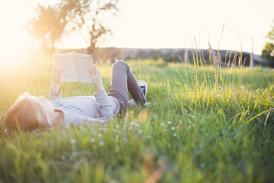 girl reading a book in the grass