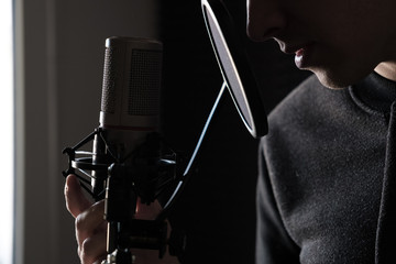 Closeup of lips and hands on a microphone of a young man standing in profile