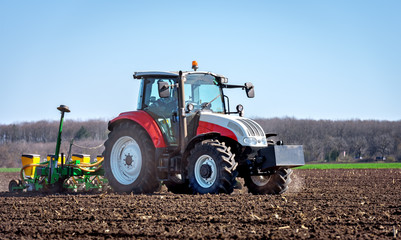 Fototapete - Agriculture tractor sowing seeds and cultivating field