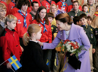 Sweden's Queen Silvia receives flowers from Hannah Sjostedt-Eriksson during an official welcoming ceremony at Rideau Hall in Ottawa