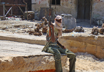 Islamist fighter holds up his rifle as he sits near checkpoint in Somalia's northern Mogadishu