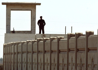 AN IRAQI SOLDIER GUARDS THE AL-QAQA MISSILES SITE SOUTH OF BAGHDAD.