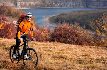 Cyclist in orange sporyive jacket riding the bike on the hill under river against beautiful mountain.