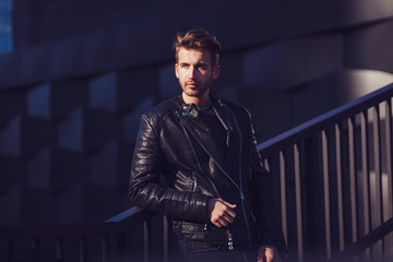 Portrait of a man in a leather jacket in urban style