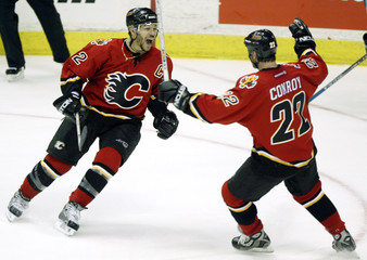 FLAMES IGINLA AND CONROY CELEBRATE GOAL BY TEAMMATE GELINAS.