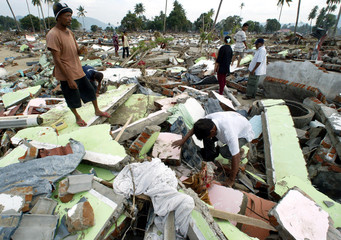Indonesians search for their belongings at their ruined house in Lhoknga.