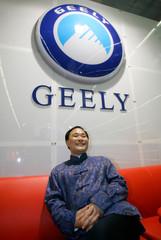 Li Shufu CEO of Geely sits under Geely logo in Frankfurt.
