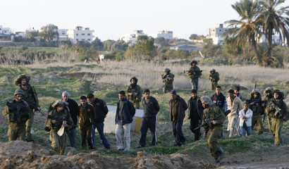Israeli soldiers lead detained Palestinians near al-Bureij