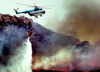 HELICOPTERS ATTEMPT TO DOUSE A FIRE SWEEPING ACROSS MOUNTAINS NEAR STELLENBOSCH.