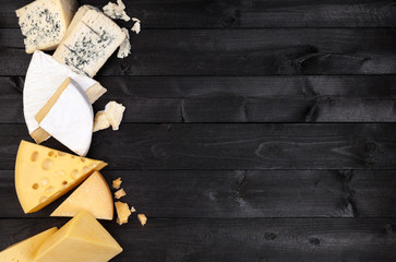Different types of cheese on black wooden table. Top view