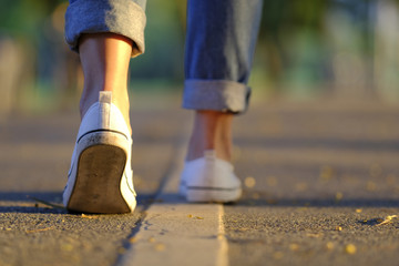 Sneaker and jeans walking on the road with beautiful sunset