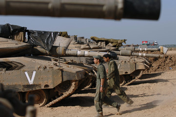 Israeli soldiers walk past tanks stationed on a military base near the Karni Crossing