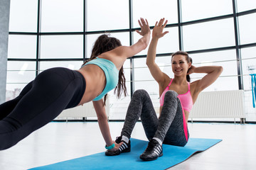 Fit smiling young woman giving high five to her personal trainer while doing abs workout on a mat in the gym