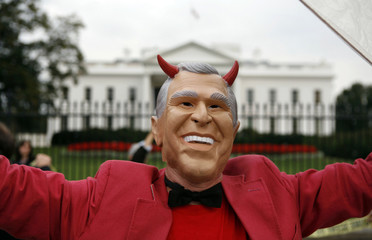 A protestor rallies while wearing a mask of U.S. President Bush with devil horns during a protest in Washington