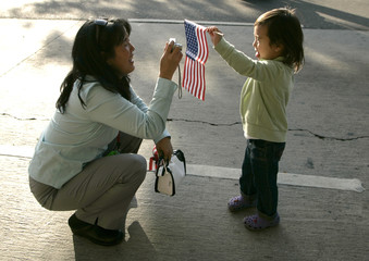 A woman takes photo of girl holding American flag during May Day immigration and labor march and rally in Los Angeles