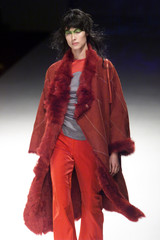 A MODEL WEARS RED COAT AND TROUSERS FOR TRISTAN WEBBER AT LONDON FASHION WEEK.