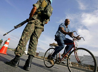 Haitian man rides bicycle past UN peacekeeper at check point in Port-au-Prince