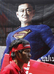 A demonstrator walks past a picture depicting ousted Thai PM Thaksin as a superhero during an anti-government protest in Bangkok