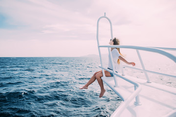 beautiful young woman sitting on the yacht nose in open sea
