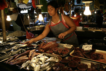 A fish vendor sorts her produce at a local wet market in Manila