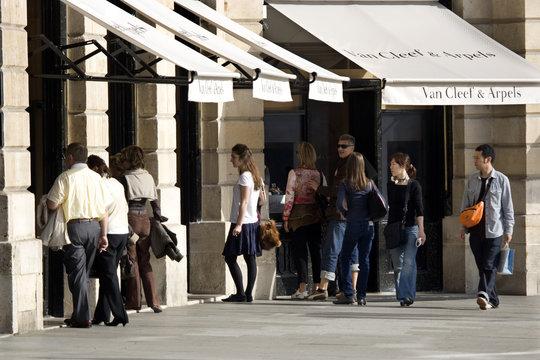 People look at a window display of luxury goods maker Van Cleef and Arpels in Paris' Place Vendome
