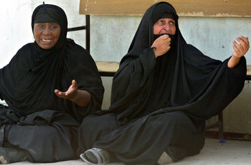 Iraqi women react as they wait outside a morgue after a car bomb attack in Sadr City