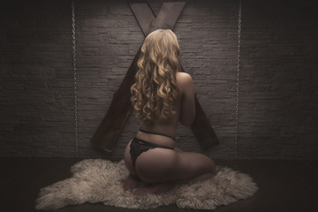 BDSM concept. blonde woman with sexy body sit on the knees near wooden cross on wall and fur on floor.