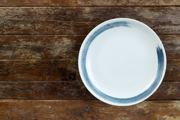 Top view of white empty ceramic plate on wooden background with copy space.