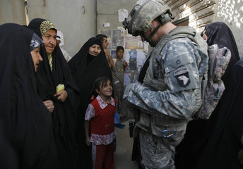 A U.S. soldier greets a child and residents asking for financial assistance from a local government office in Samarra