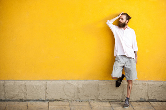 Tattooed fashion bearded hipster on yellow wall posing outdoor