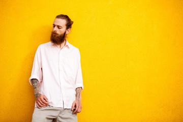 Tattooed bearded man on yellow wall posing outdoor