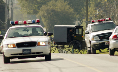 An Amish horse-drawn buggy navigates between police cars near the crime scene of a one-room schoolhouse in Nickel Mines