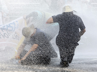 Protesters are hit by water on a street in Pyeongtaek
