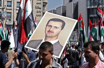 Demonstrators carry photo of President al-Assad and Syrian flags in Damascus