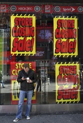 """A man uses his phone in front of """"Store Closing Sale"""" signs at the Virgin Mega Store in New York's Times Sq."""