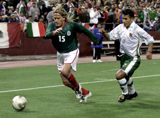 MEXICO'S HERNANDEZ DRIBBLES BALL PAST BOLIVIA'S COLQUE DURING FRIENDLYMATCH.