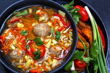 Soup with meatballs in a black plate, sliced vegetables - onion, parsley, pepper, tomato on a black background