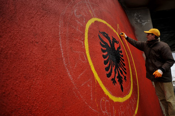 An ethnic Albanian worker from Kosovo draws an Albanian flag near the town of Urusevac, southeast of the capital Pristina