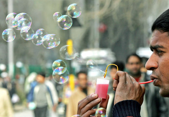 An Indian vendor makes soap bubbles from an improvised pipe in Srinagar, March 24, 2006...