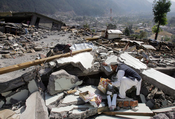 A Kashmiri earthquake survivor searches his belongings on the debris of his house in Balakot